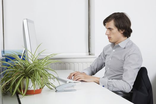 Young businessman typing at office desk