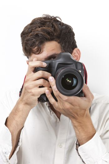 Young man taking photograph with vintage camera against white background