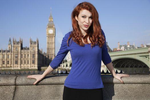 Portrait of beautiful young woman standing against Big Ben clock tower, London, UK