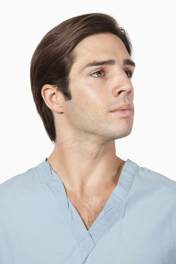 Young man in surgical scrubs against gray background