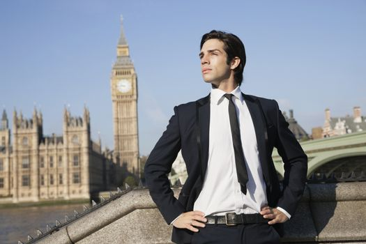 Confident young businessman standing against Big Ben clock tower, London, UK