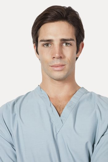 Portrait of confident young man in surgical scrubs over gray background