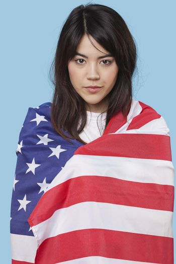 Patriotic young woman wrapped in American flag over blue background