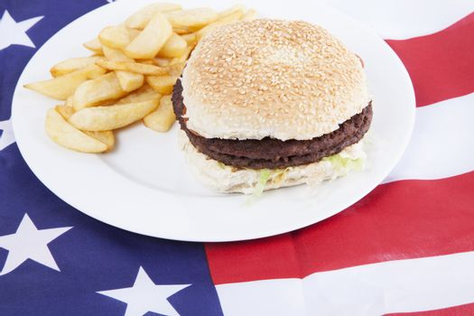 Cropped shot of chips and burger over America flag