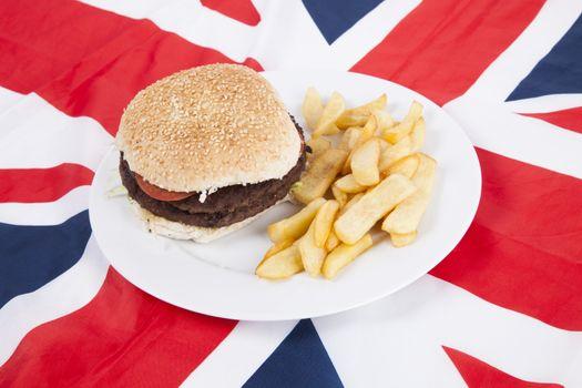 Close-up of hamburger and chips over British flag