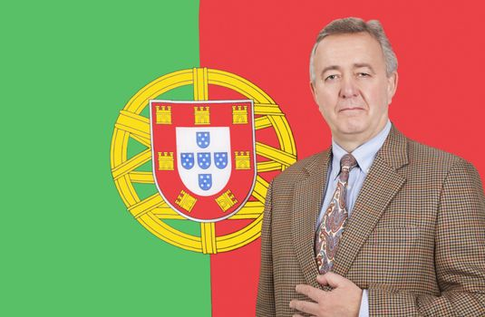 Portrait of middle-aged businessman standing over Portuguese flag