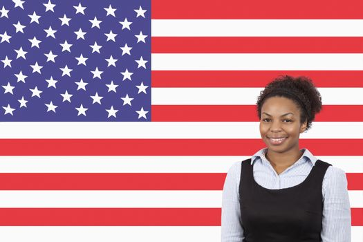 Young African American businesswoman smiling over American flag