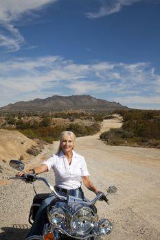 Senior woman riding motorcycle on desert road