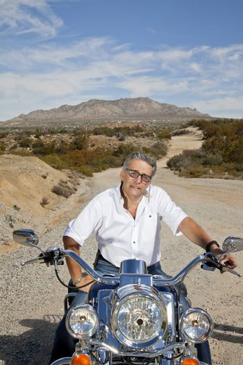 Senior man sits on motorcycle and looks at camera on desert road