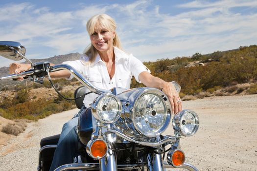 Senior woman sits on motorcycle on desert road
