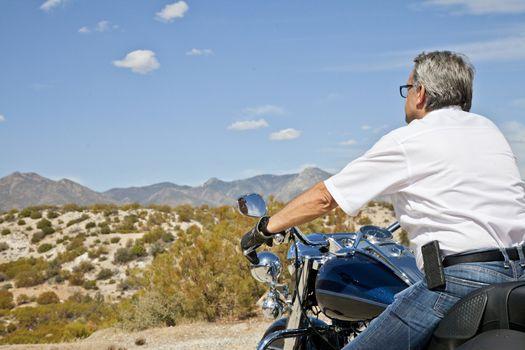 Senior man riding motorcycle through the desert