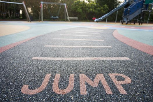 """Jump"" written into rubber floor of playground"