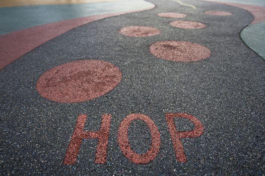 """Hop"" written into rubber floor of playground"