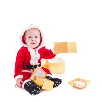 Little Santa boy with gold gift boxes isolated on white background