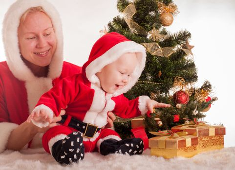 Christmas baby and mom open gifts under the fir tree