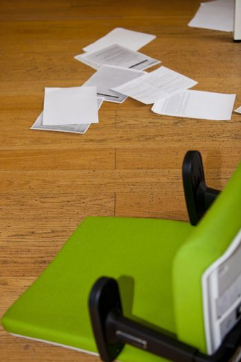 Green chair and paperwork on the floor