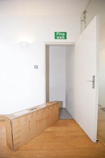 """Cardboard box marked """"fragile"""" by fire exit"""