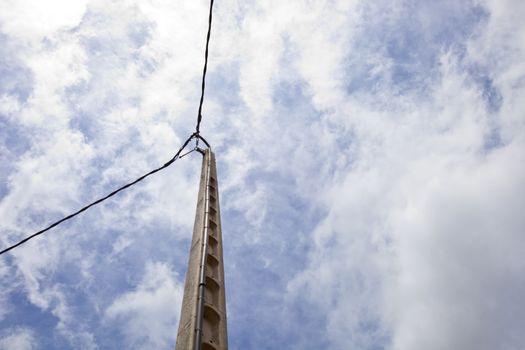 Power line against blue sky and sun