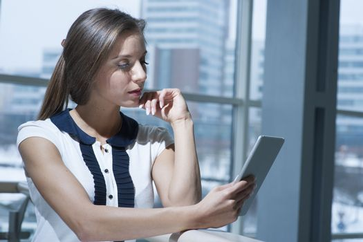 Pensive businesswoman reading from digital tablet
