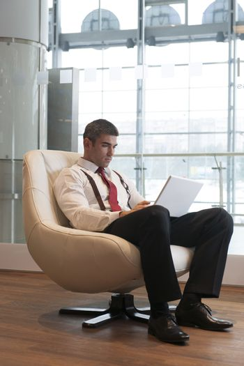 Businessman in arm chair working on laptop