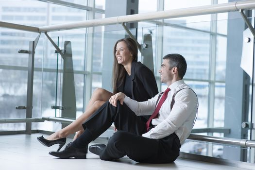 Male and female coworkers sitting and joking together
