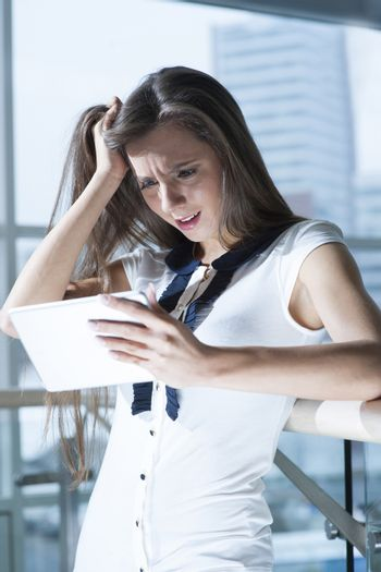 Shocked businesswoman reading tablet device