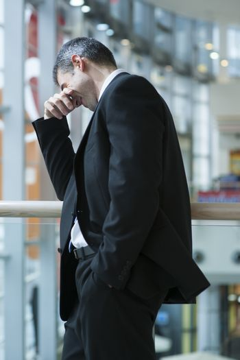 Businessman smirking and covering eyes