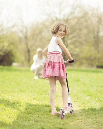 Young girl riding scooter through park with mother in background