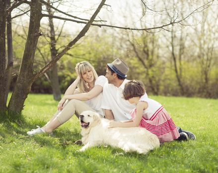 Family sitting in park with dog