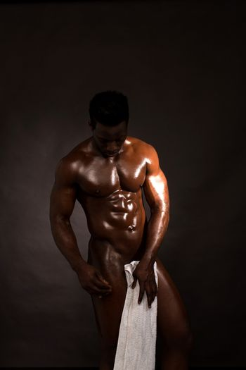 Wet muscular man wiping himself with a towel
