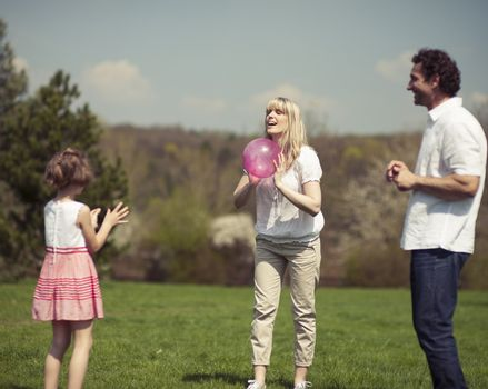 Family throwing ball to each other in the park