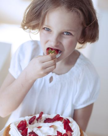 Close-up of Young girl with cake eating strawberry