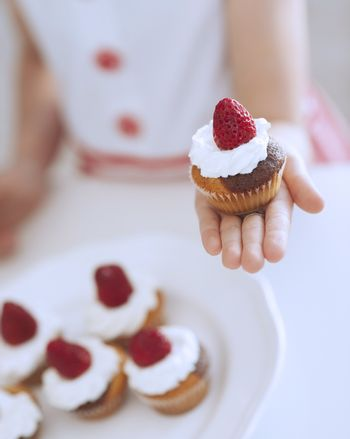 Young girl holding cup cake