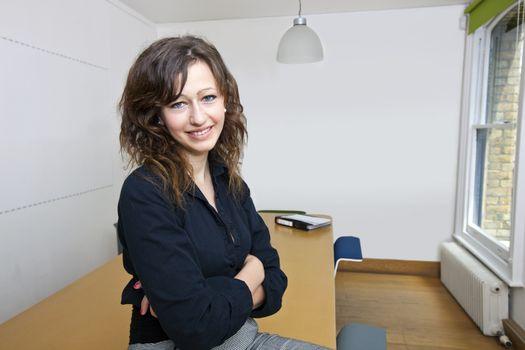 Proud businesswoman sitting in her board room
