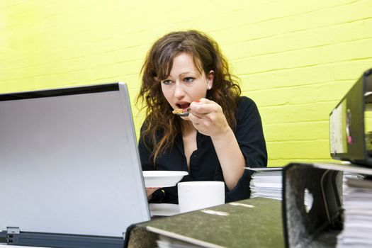 Caucasian young woman eating and working on her laptop computer at her desk