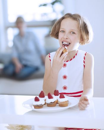 Young girl eating cup cake