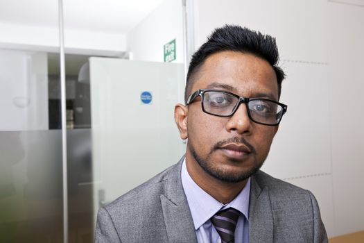 Close-up portrait of Indian Businessman wearing glasses with beard