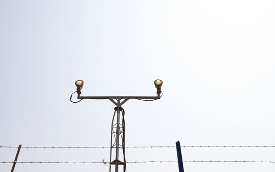 Lighting equipment at the start of airport runway surrounded by barb wire