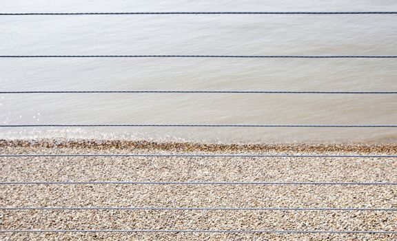 River Thames and Shingle beach behind wire rope fence