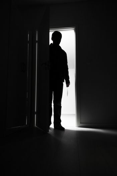 Full-length of burglar entering into house