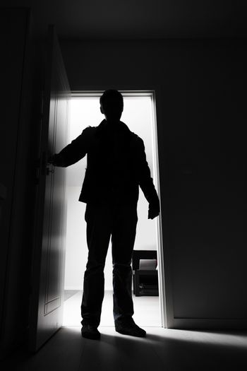 Full-length of thief entering into house