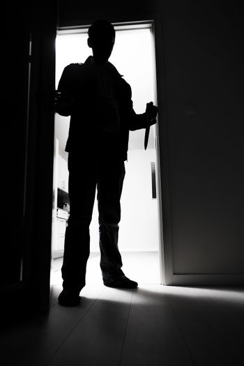 Full-length of thief with knife entering into dark room