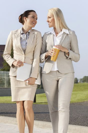 Young businesswomen with disposable cup and laptop walking on street