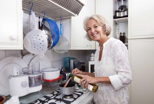 Portrait of senior woman adding olive oil to saucepan at kitchen counter