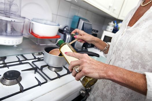 Cropped image of senior woman adding olive oil to saucepan at kitchen counter