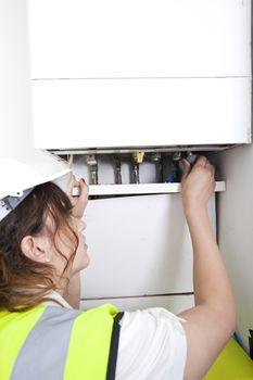 Female plumber servicing central heating boiler