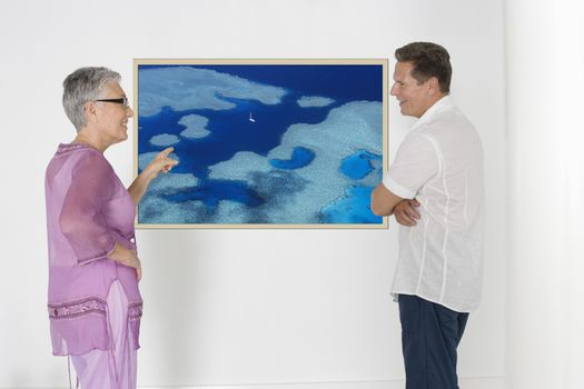 Couple discussing vacation plans against white wall with photograph