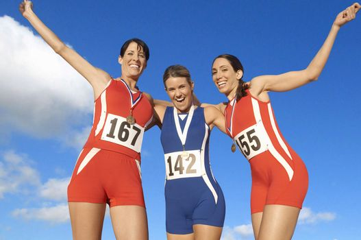 Victorious track athletes with arm around each other against sky