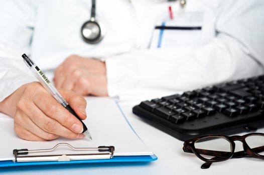 Cropped image of a physician writing prescription