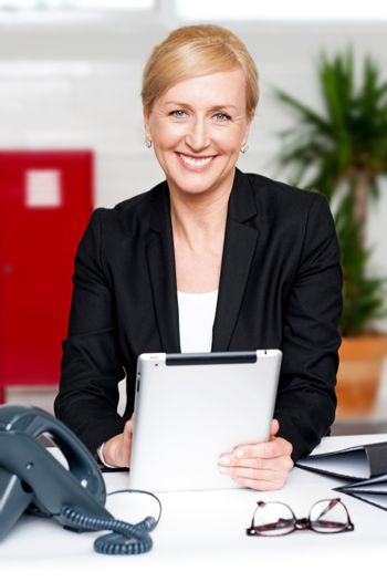 Businesswoman with tablet pc at her desk